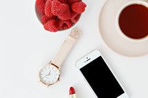 Raspberries in a bowl, iPhone, lipstick, watch, magazine, rings, spoon, and coffee cup