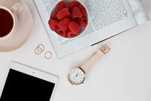 Raspberries in a bowl, watch, tablet, magazine, rings, and coffee cup