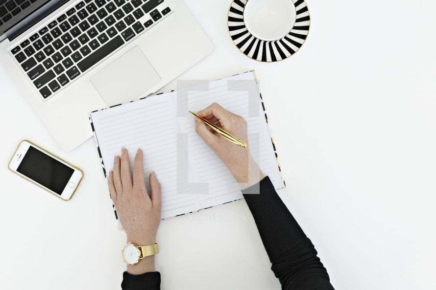 a woman writing in a planner