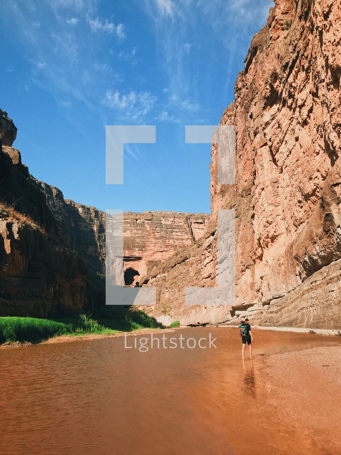 man walking through a river at the bottom of a canyon