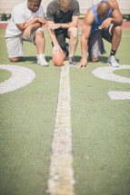 men in prayer on a football field
