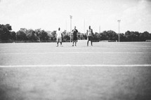 three men standing on a football field