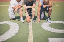athletes kneeling in prayer on the football field