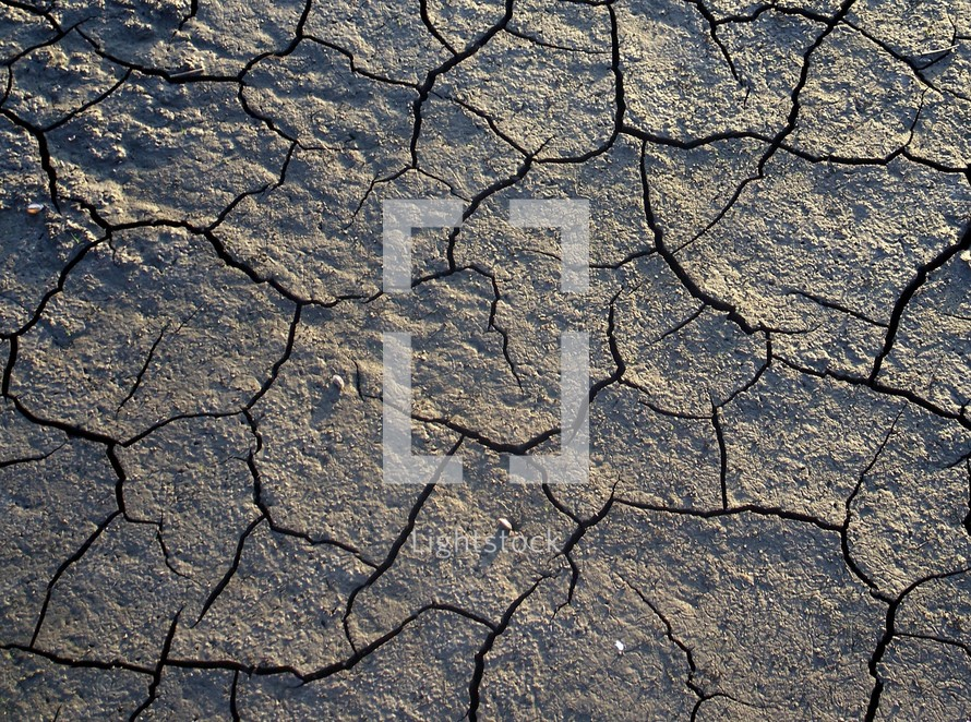 A dry river bed affected by drought and lack of rain shows the cracked dry earth that brings drought, famine and starvation to many throughout history.