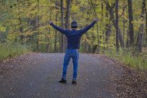 a man standing on a country road with arms raised