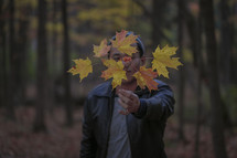 a man holding a branch full of fall leaves in front of his face