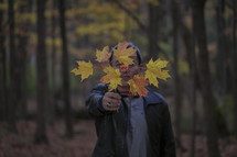 man holding a branch full of fall leaves in front of his face