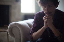 a man sitting on a couch in prayer
