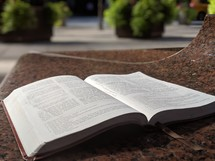 open Bible on a table outdoors