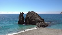 giant rock along a shore in Italy