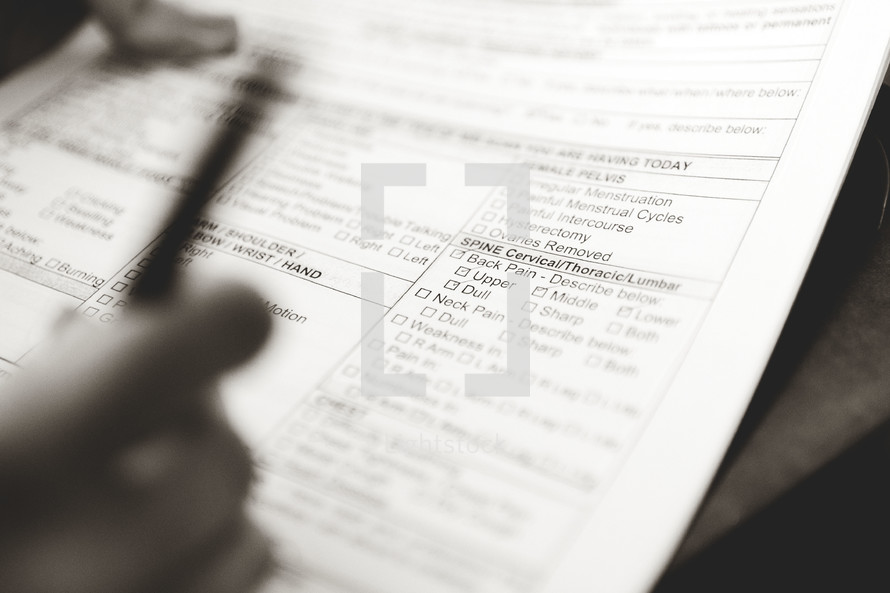a man filling out medical forms at a doctors office