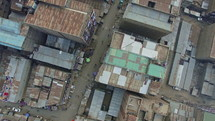 aerial view over rusty tin roofs in a busy town