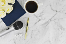 notebook, earbuds, coffee mug, roses, microphone, and pen on a marble background