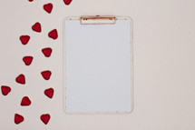 red heart shaped chocolates and white paper on a clipboard