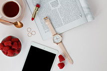 Raspberries in a bowl, watch, magazine, rings, tablet, lipstick, spoon, and coffee cup