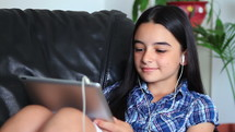 Smiling girl listening to music holding a tablet pc in hands