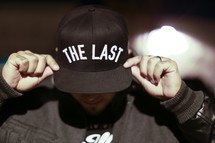 man wearing a hat with the words the last