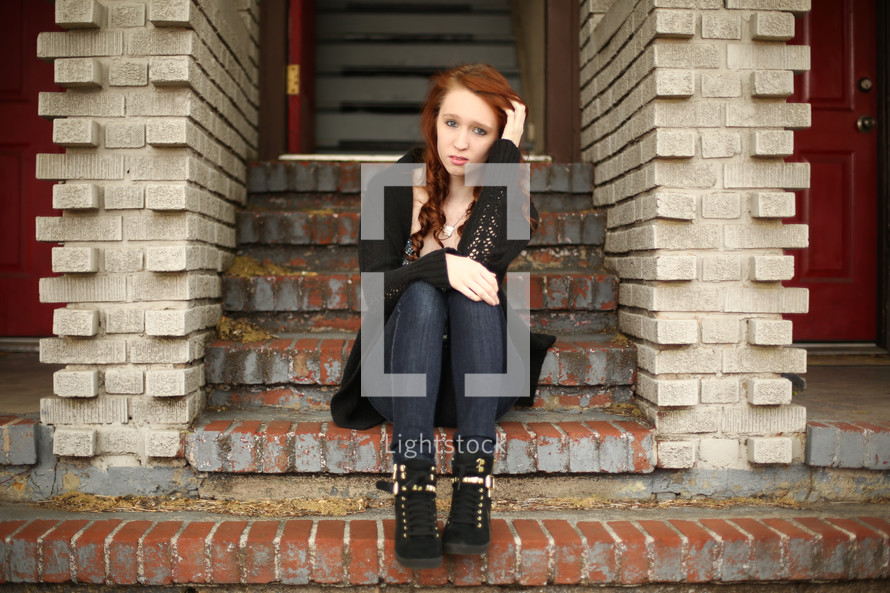 a confused teen girl sitting on brick stairs