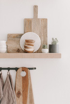 wooden cutting boards on a floating shelf