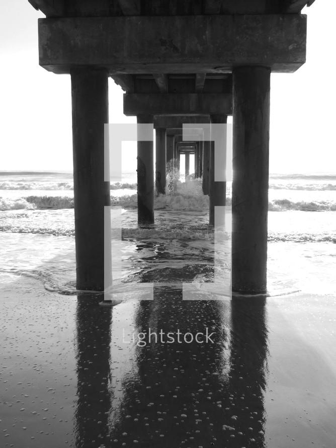 stone pillars under an ocean pier