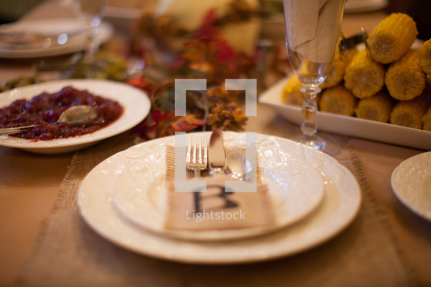 place settings and food on a Thanksgiving dinner table