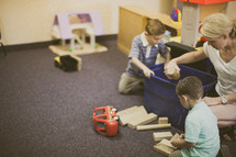 nursery staff and toddler boys playing with blocks