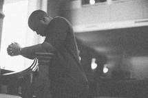 Kneeling man in prayer.