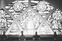 stained glass window of Jesus in a church and a congregation