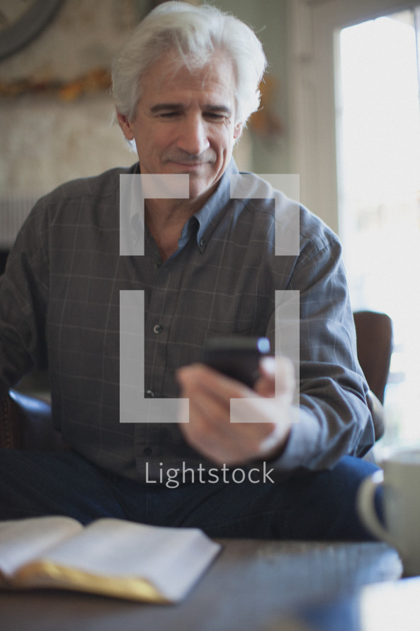 man looking at his cell phone with an open Bible