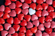 single white heart shaped candy and red and pink candy