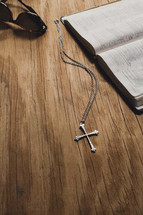 A cross on a chain, sunglasses and an open Bible on a wooden tabletop.