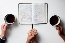 couple praying together with an open Bible and coffee mug