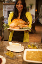 woman carrying a Thanksgiving turkey to a dinner table