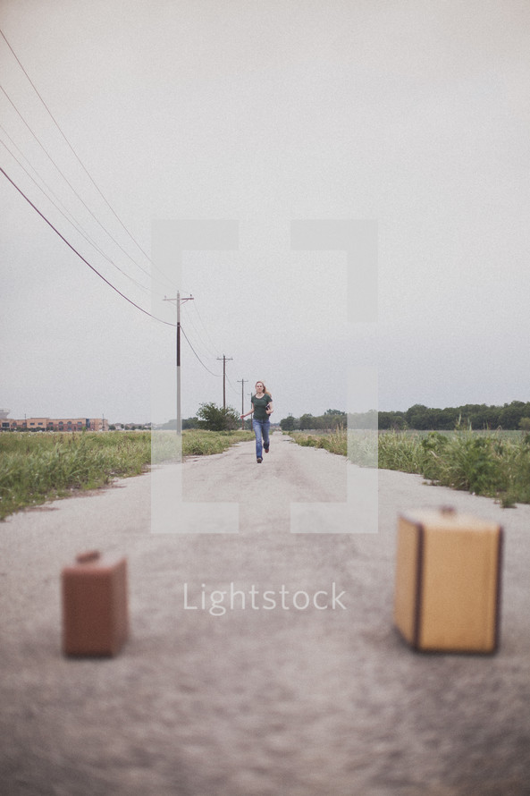 woman running down a long road towards two suitcases