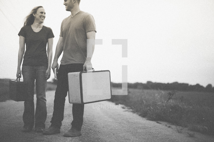 man and woman standing in the middle of a road carrying suitcases