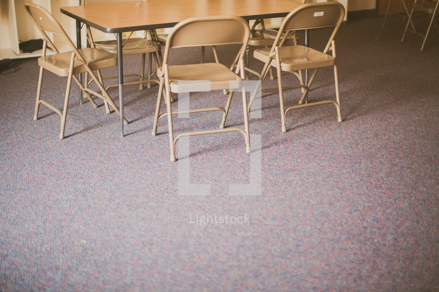 chairs under a table in an empty classroom