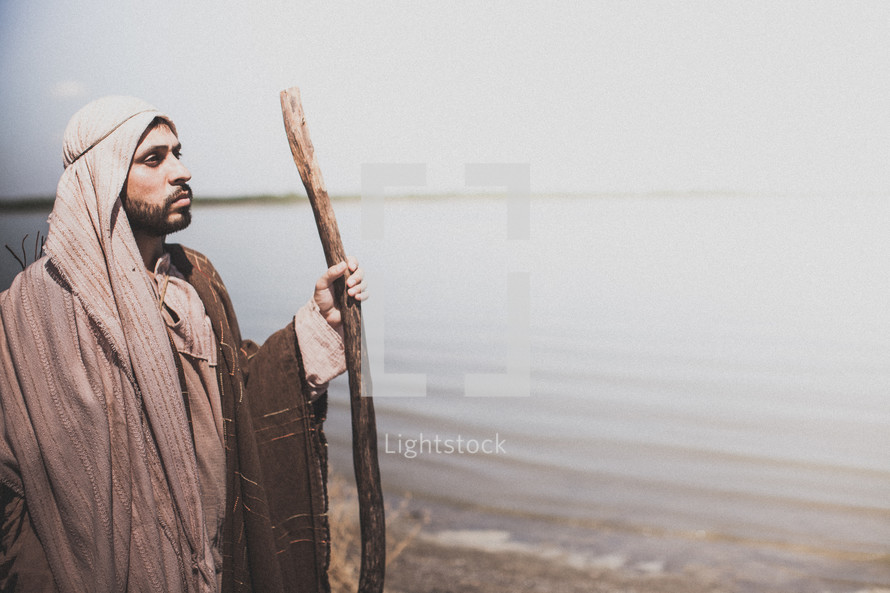 Paul holding a staff standing by water