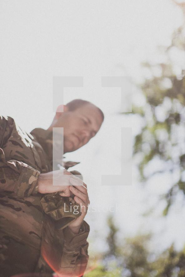 serviceman in prayer holding his cap