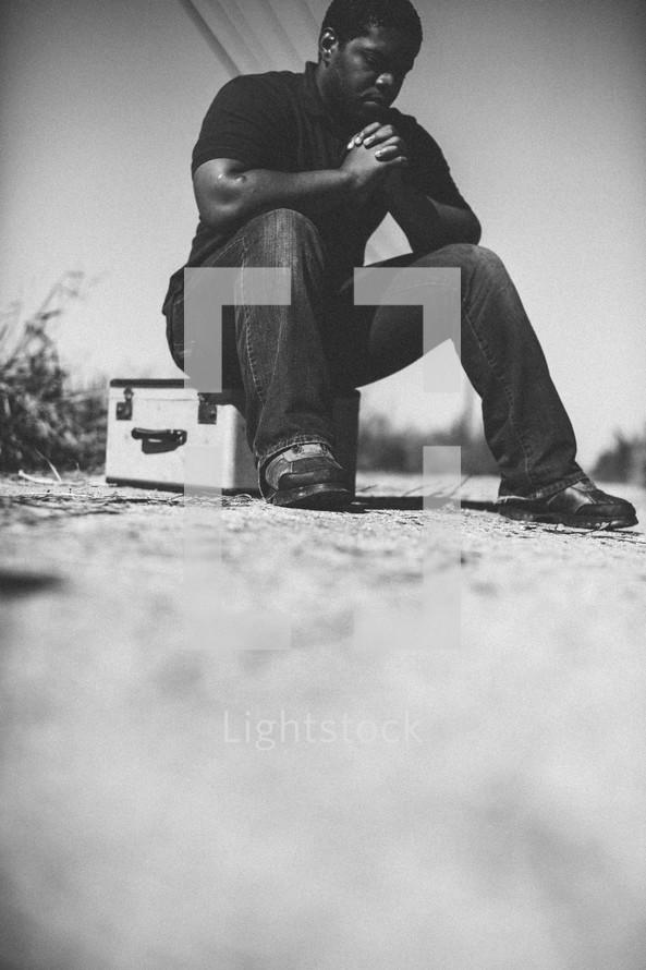 man in prayer sitting on luggage