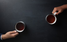 hands holding coffee mugs