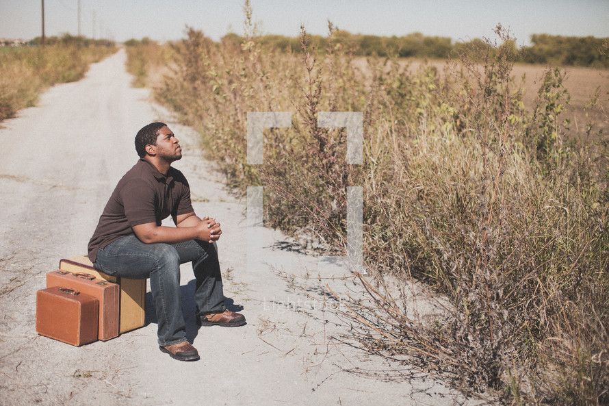 man sitting on luggage on a dirt road praying