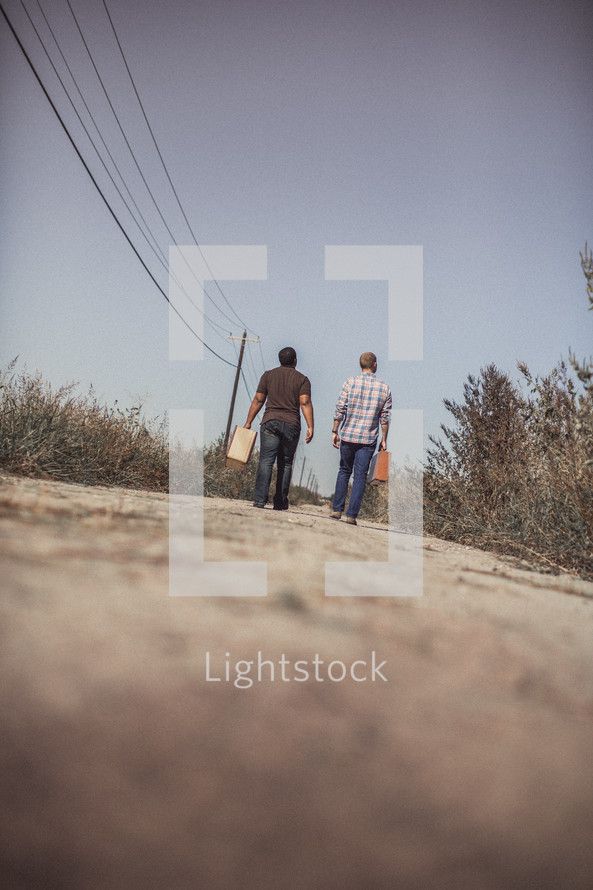 men walking down a dirt road