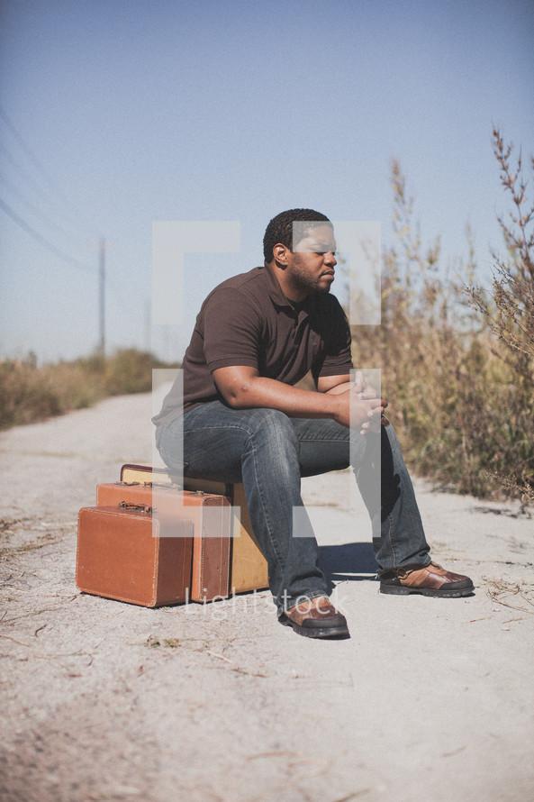 man sitting on luggage praying on a dirt road
