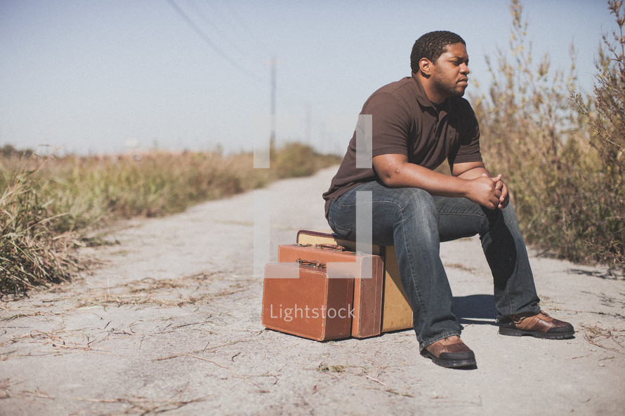 man sitting on luggage on a dirt road