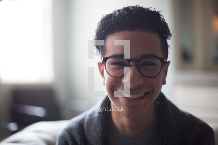 smiling young man in reading glasses