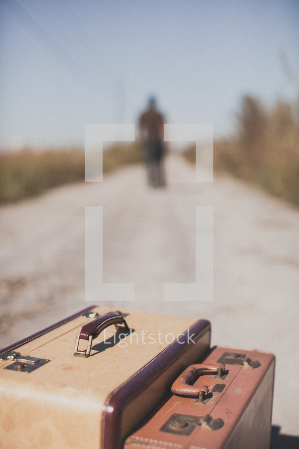 luggage and a man walking away down a dirt road