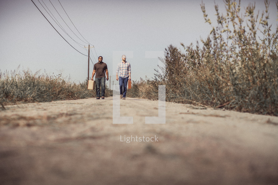 men walking down a dirt road with luggage