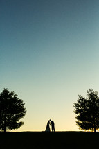 silhouette of a bride and groom kissing