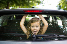 Little girl looking through back car window