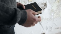 addict holding a needle and a Bible